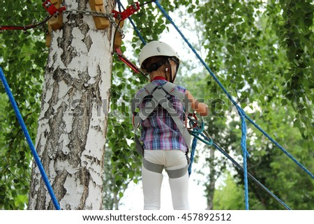 girl in a rope Park. rides in the nature