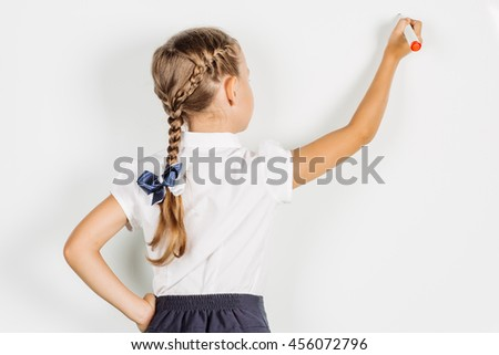 girl in a school uniform writing something on board with a marker. Learning and school concept. Image on white background. - stock photo