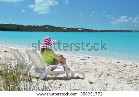 Girl in a striped hat on the beach of Exuma, Bahamas - stock photo