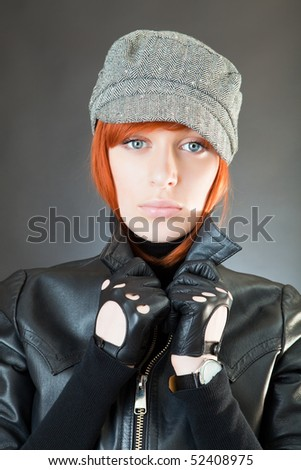 Girl in a suit of the biker against a dark background