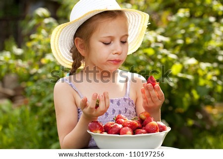 Girl in a summer hat and dress eating fresh strawberries - stock photo