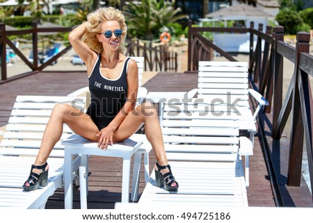 girl in a swimsuit and sun glasses sitting on the beach and laughing