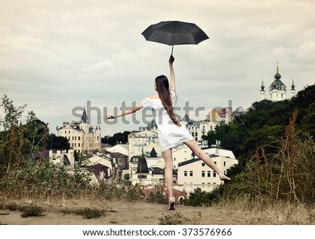 Girl in a white dress with umbrella on the hill at the old town - stock photo