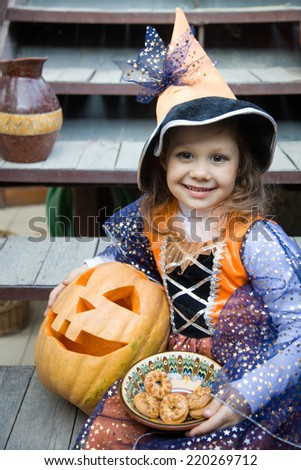 girl in a witch costume with halloween pumpkin on holiday - stock photo