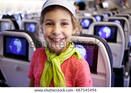 girl in an airplane cabin on a background of screens in seatback