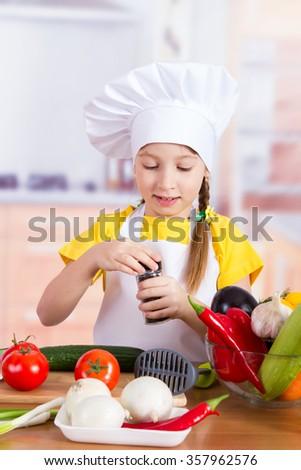 girl in an apron holding a jar with spices on the table