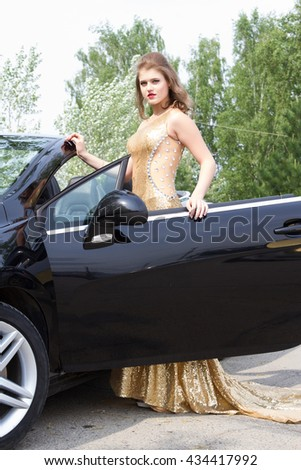 girl in an evening dress on a background cabriolet
