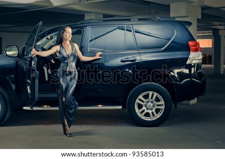 girl in an underground garage with a car