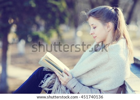 girl in autumn park with a book - stock photo
