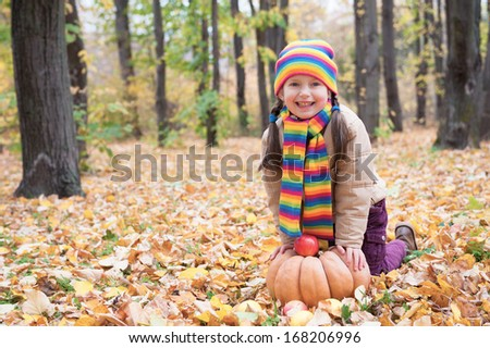 girl in autumn park with pumpkin and apples