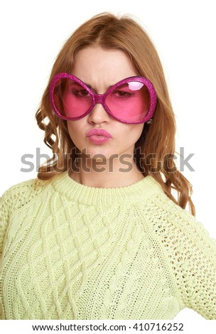 girl in big pink eyeglasses of hearts shape, dressed jeans and a green sweater posing in studio on white background