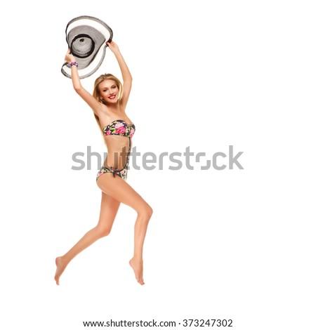 Girl in bikini holding summer hat - stock photo