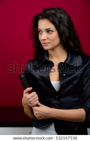 girl in black and white dress with tablet on red background - stock photo
