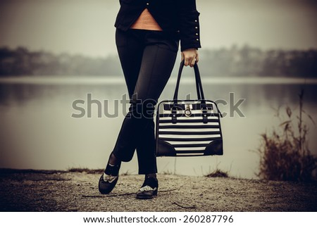 Girl in black and white shoes with black and white bag in her hands outdoor - stock photo