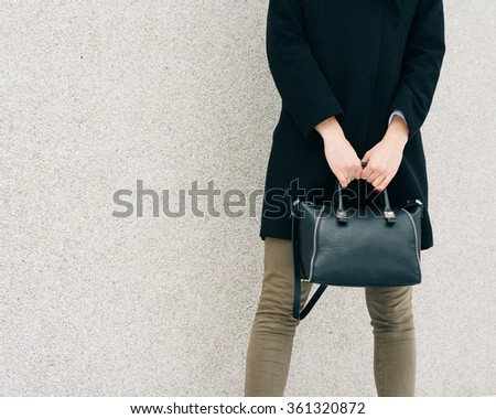 Girl in black coat, green jeans and a bag in her hand stands on a background of beige wall. Copy space.