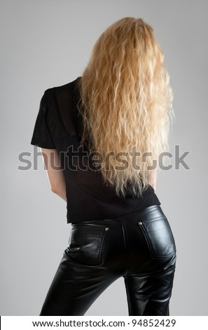 Girl in black leather pants, with beautiful long hair. - stock photo