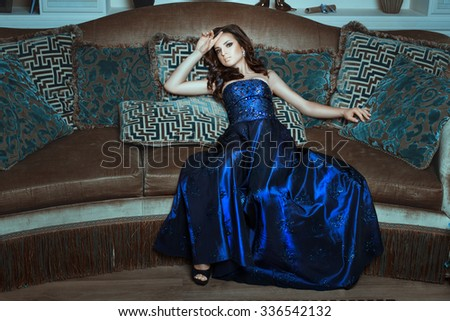 Girl in blue and shiny dress posing lying on the couch. Her long hair lying on the bare shoulders. - stock photo