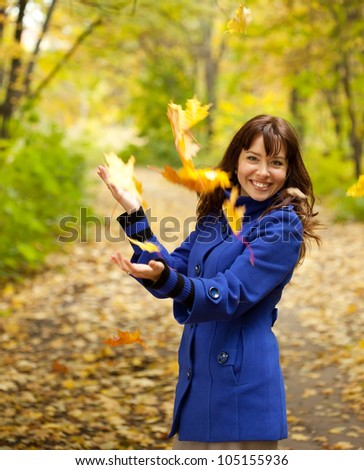 Girl in blue coat throwing leaves in the air - stock photo