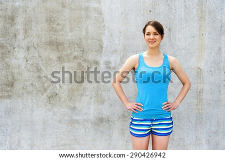 Girl in blue tank top and shorts over the wall smiling. - stock photo