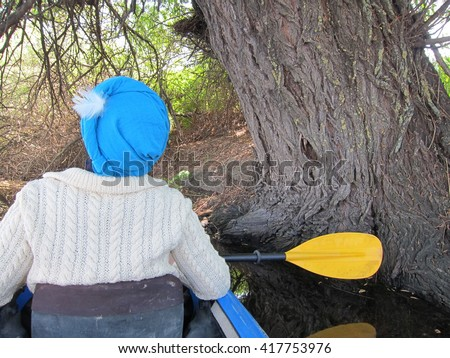 Girl in blue turban and with yellow paddle in a kayak