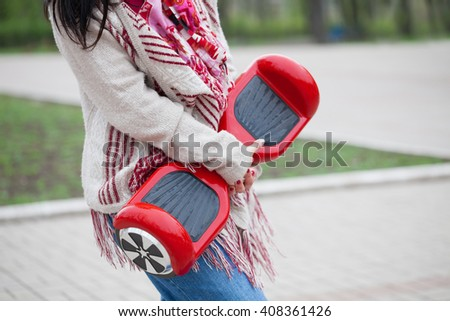 Girl in boho style clothes holding modern red electric mini segway or hover board scooter in hands while walking in the park. Popular new gadget,that produces no air pollution to the atmosphere.  - stock photo