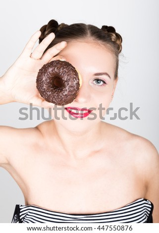 girl in bright makeup eating a tasty donut with icing. Funny joyful woman with sweets, dessert. dieting concept. junk food. girl looking through donut hole - stock photo