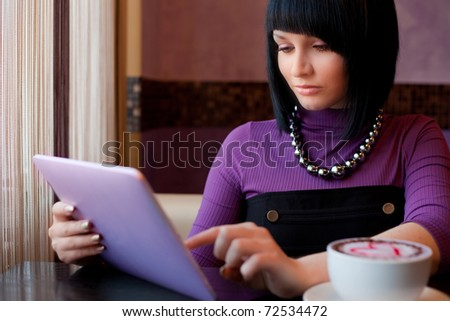 girl in cafe uses small mobile computer