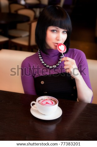 girl in cafe with coffee eat lollipop - stock photo