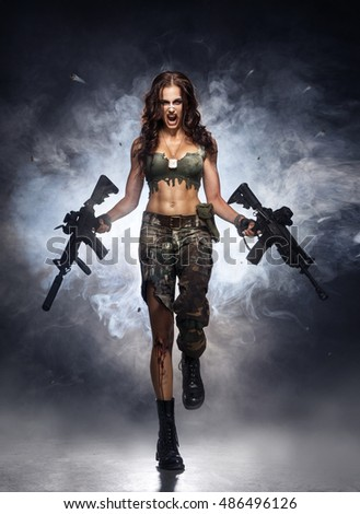 Girl in camouflage running through the smoke with two guns