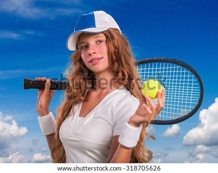 Girl in cap holding tennis  racket and ball on blue sky with clouds.