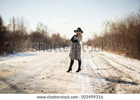 girl in coat and hat on the road