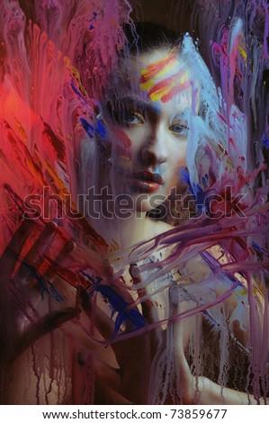 girl in color paint behind the painted glass - stock photo
