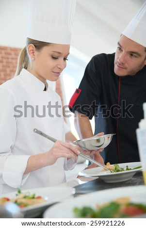 Girl in cooking training class with chef - stock photo