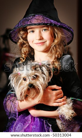 Girl in costume of witch with dog