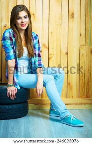 Girl in country style sitting on auto tires against yellow wooden wall. Smiling model with long hair.
