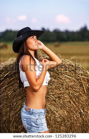 Girl in cowboy hat and jeans shorts with straw. - stock photo