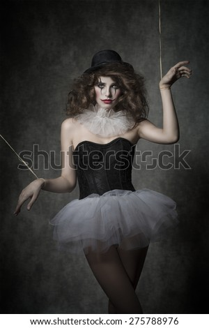 girl in creative fashion shoot with gothic atmosphere. She is wearing like horror puppet with vintage tutu, bowler hat and clown make-up. - stock photo