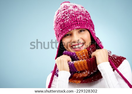 Girl in crimson knitted winter cap and scarf looking at camera with smile - stock photo