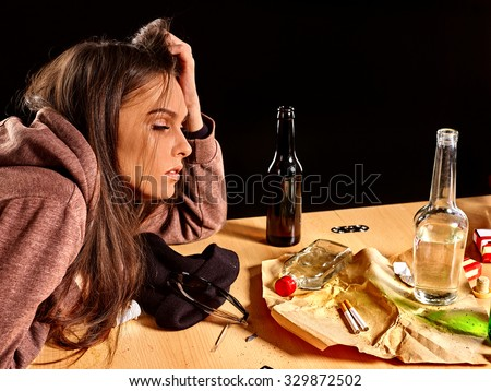 Girl in depression drinking alcohol and smokes cigarettes in solitude at the table. - stock photo
