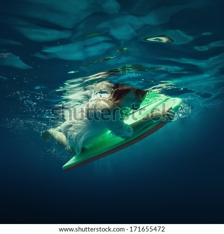 Girl in dress diving under water with a surfboard.