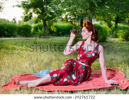 Girl in dress sitting on the grass and looking through binoculars. Retro