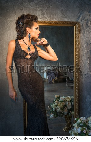 Girl in dress standing near a vintage mirror - stock photo