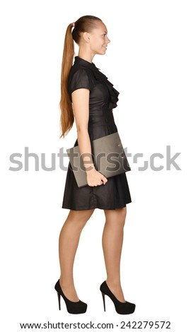 Girl in dress standing sideways holding a clipboard - stock photo