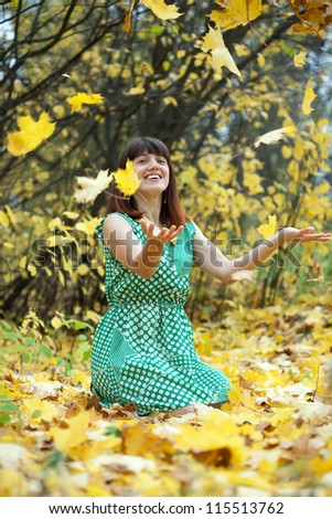 Girl in dress throwing maple leaves in the air - stock photo