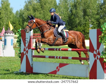 Girl in equestrian uniform on horseback jumping hurdle - stock photo