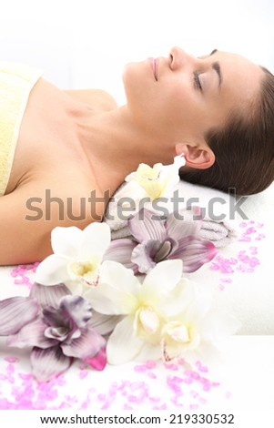 Girl in flowers.Aromatherapy massage Woman relaxes in a beauty salon. - stock photo