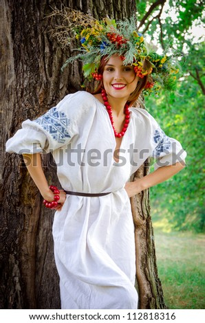 girl in flowers wreath and traditional clothes - stock photo