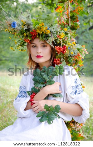 girl in flowers wreath and traditional clothes