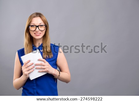 Girl in glasses shows holding in hands notebook for records. Young beautiful modern woman. Various women's emotions. Attractive cheerful young woman in glasses pointing at space over gray background.  - stock photo
