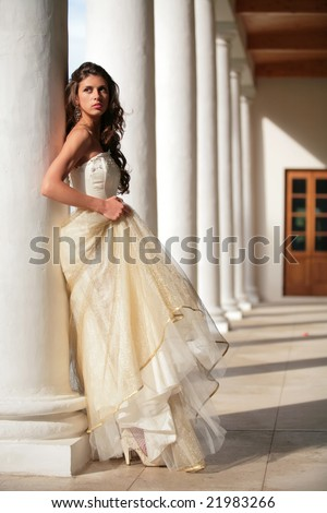 girl in golden gown amongst pillars of the old-time building - stock photo
